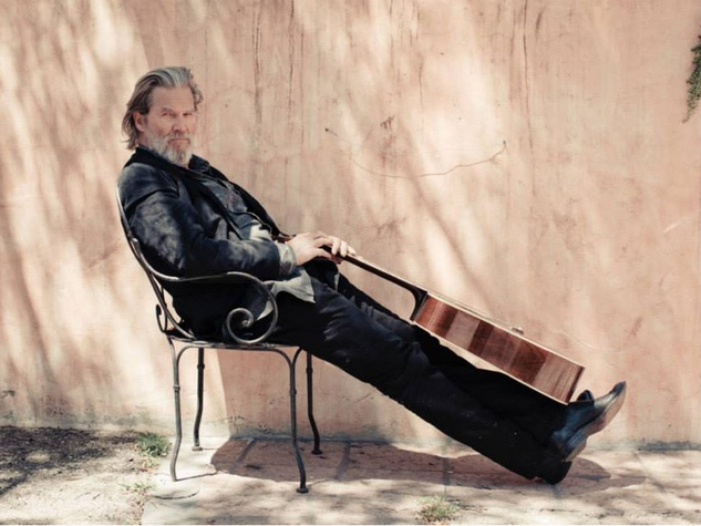 Jeff Bridges sitting in chair with guitar