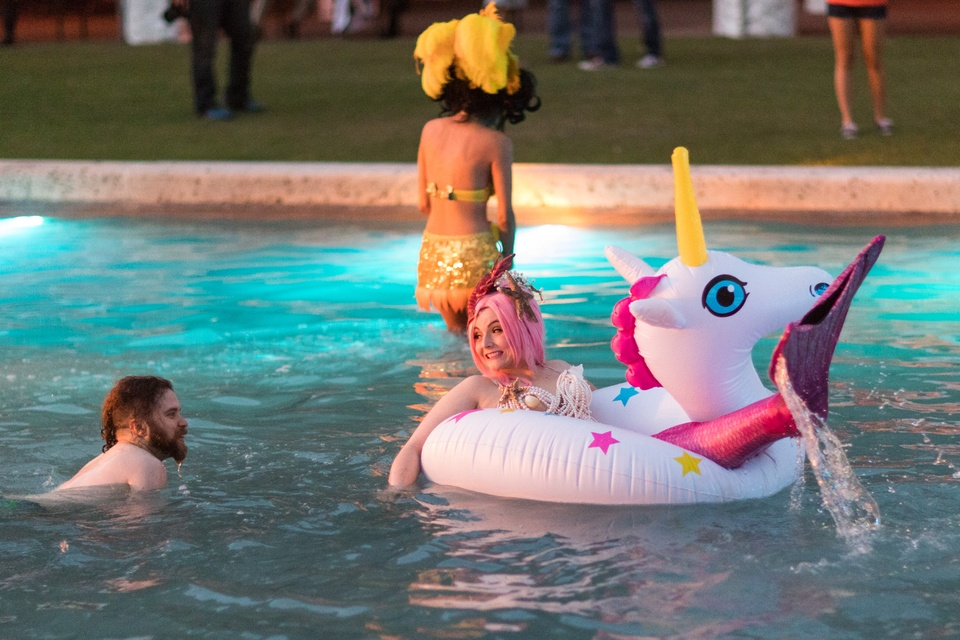 A mermaid and unicorn floats past some swimmers from Bayou City Burlesque performing in the City Hall reflection pool during the Legendary Art Car Ball