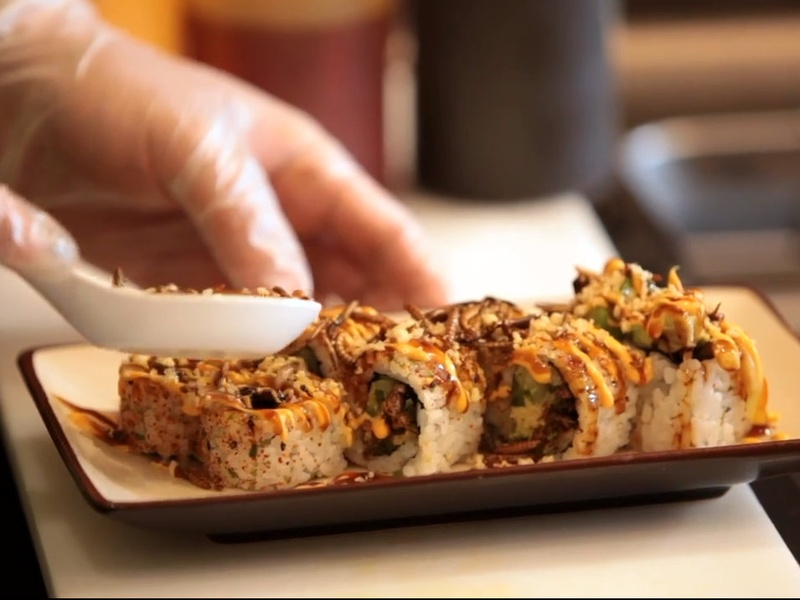 Chef Peter Yung sprinkles on mealworm tempura flakes on insect bug sushi roll