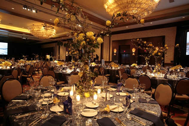54 Yellow rose centerpieces at the venue at An Evening with a Legend February 2015