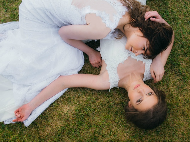 Two brides lying in the grass