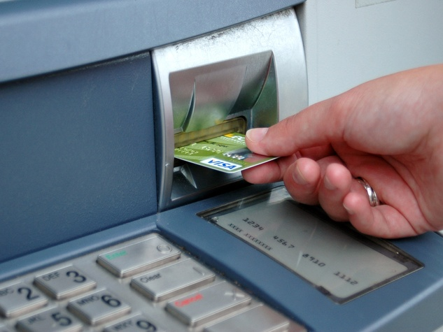 using an ATM with hand holding credit card