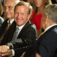Chairman of Points of Light Neil Bush (C) shakes hands with his father, former US President George H.W. Bush, while attending a White House ceremony to recognize the Points of Light volunteer program July 15, 2013