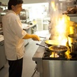 L'Olivier Restaurant chef Olivier Ciesielski in kitchen cooking with flaming stove