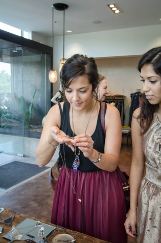 Cristina Facundo tries on a ring while her sister Sara looks on at By George