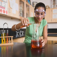 Houston Area Urban League student in chemistry class with beaker
