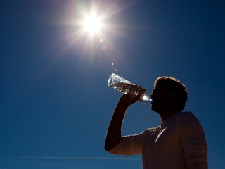 silhouette of man drinking water in hot sun blue sky