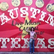 cropped Mickey Avalon shirtless in front of Austin mural