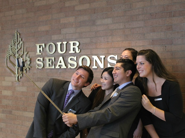 Four Seasons Hotel staff member demonstrate proper use of a Selfie Stick
