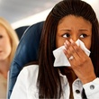 sick on airplane women holding tissue to nose