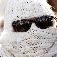 person with face wrapped in cold weather and wearing sunglasses