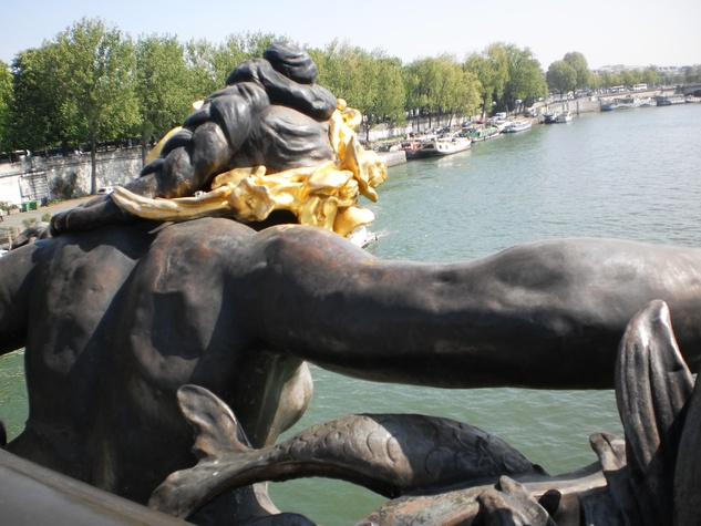Looking down the Seine over the shoulder of nymph sculpture decorating Pont Alexandre III in Paris