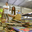 Students from Sharpstown International High School in HISD sort books at the Books Between Kids warehouse