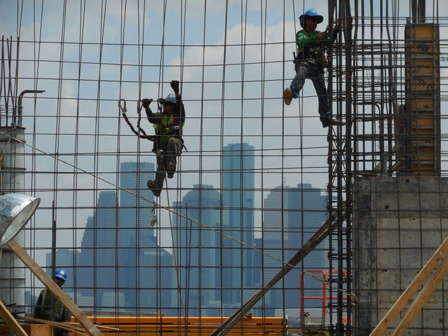 construction workers with Houston skyline in background