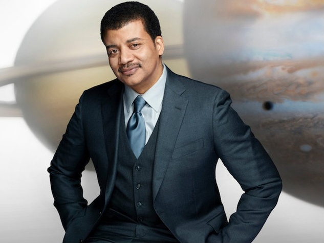astrophysicist and scientist Neil deGrasse Tyson in front of planets
