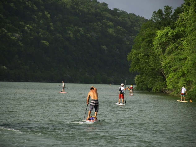single paddleboarder on lake for Tyler's Dam That Cancer