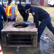 DAS employees at storm drain rescuing puppy