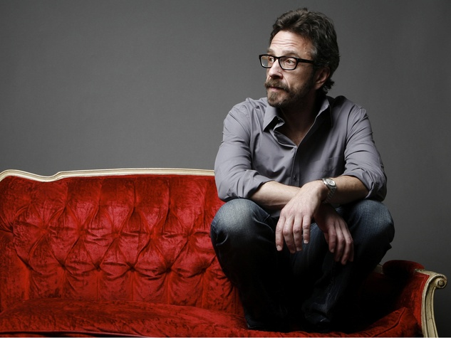 comedian Marc Maron sitting on a couch
