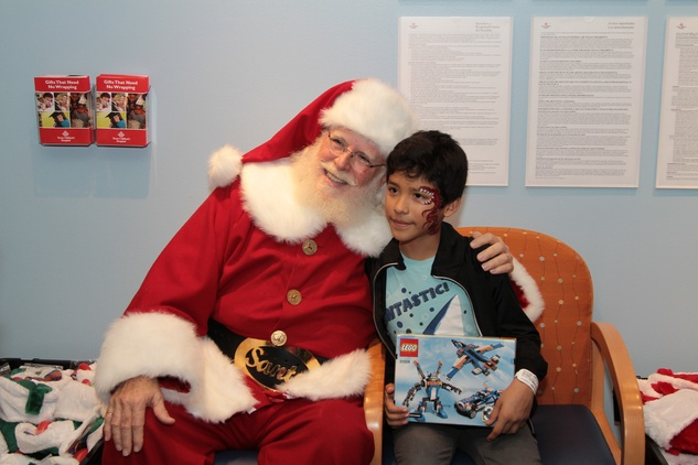 35 A patient smiles with Santa after receiving a gift at Santa visits Texas Children's Cancer Center December 2014