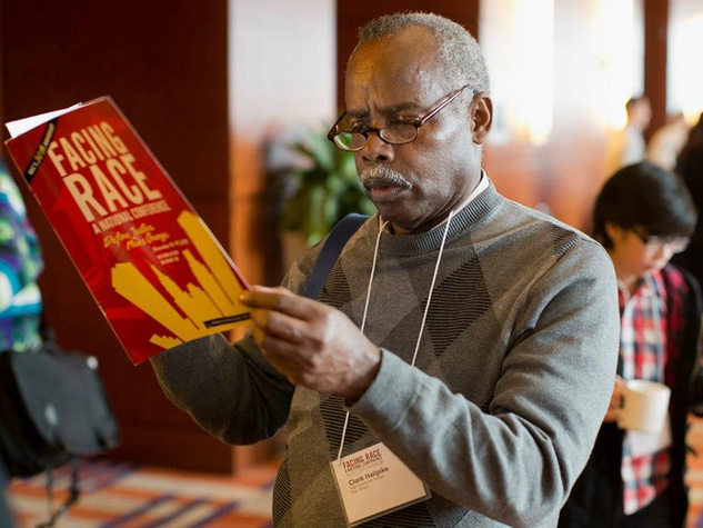 A man reads a Facing Race program