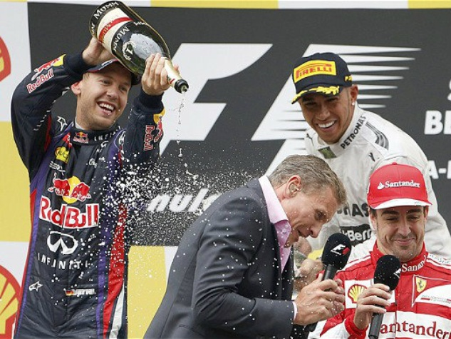 BBC Television pundit David Coulthard gets a soaking from Sebastian Vettel and Lewis Hamilton