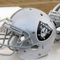 Oakland Raiders football helmets on bench