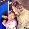 Man and a baby using Robocoin bitcoin ATM