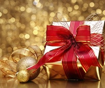Holiday gift wrapped in gold with red bow