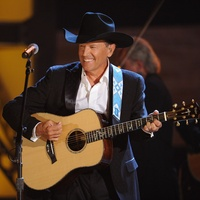 George Strait, with guitar, smiling