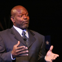Emmitt Smith, in suit, speaking
